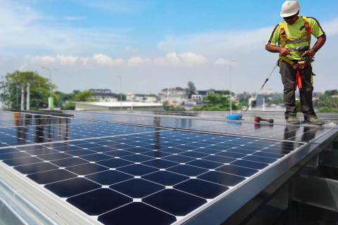 Station-service Total au Nigéria. Un ouvrier portant un casque travaille à l'installation de panneaux solaires Sun Power sur le auvent de la station-service.